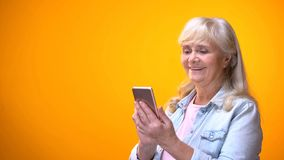 Happy elderly lady using smartphone, searching online medical service, shopping royalty free stock image