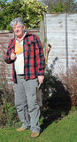 Happy elderly male gardener. A happy elderly male gardener with his spade during a gardening session in his backyard Royalty Free Stock Photos