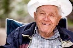 Happy Elderly Man. A portrait of a happy smiling elderly man sitting outdoors stock photo
