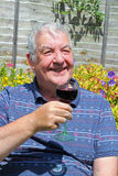 Happy elderly man drinking a glass of wine. Stock Photos
