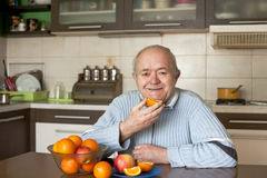 Happy elderly man eating fruit. Seniors-fruit-healthy eating royalty free stock photos