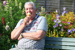 Happy elderly man eating an ice ream Royalty Free Stock Images