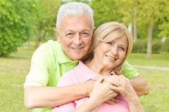 Happy elderly man embracing senior woman Stock Images