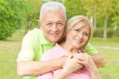 Happy elderly man embracing senior woman Stock Images