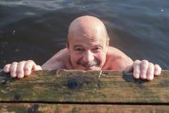 Happy elderly man enjoying active summer vacation. Healthy senior man swimming in the lake or river. Happy elderly man enjoying active summer vacation stock image