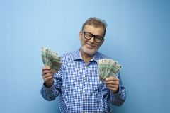 Happy elderly man in glasses holds banknotes stock photos