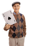 Happy elderly man holding a big ace of spades card Royalty Free Stock Photos