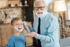 Happy elderly man holding shaving foam. Time for shaving. Happy nice elderly men holding shaving foam and smiling to you while standing together with his Stock Photos