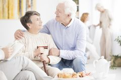 Happy elderly man hugging wife Stock Image