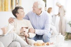 Happy elderly man hugging wife Stock Image