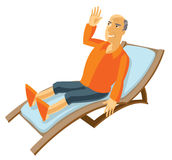 Happy elderly man lying on the sun lounger Stock Photos