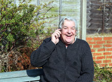 Happy elderly or old man on a mobile phone. Stock Photography