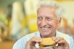 Happy elderly man. Portrait of happy elderly man eating fast food royalty free stock photos