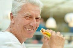 Happy elderly man. Portrait of happy elderly man eating fast food royalty free stock photo