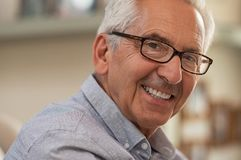 Happy elderly man. Portrait of smiling senior man with eyeglasses looking at camera. Successful mature man wearing spectacles at home. Closeup face of handsome royalty free stock photo