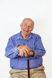 Happy elderly man sitting in a chair Stock Images