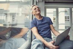 Happy elderly man sitting with gadget on knees Stock Photo