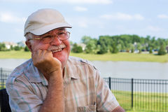 Happy elderly man sitting on an outdoor patio Royalty Free Stock Images