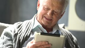 Happy elderly man is using tablet computer at home stock footage