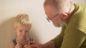 Happy elderly man washes his hands on tap from his hand and face to his little son and wipes him with towel. father takes care of stock video