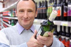 Happy elderly man with wine bottle. Happy elderly man in shop with wine bottle in hands royalty free stock photography