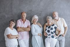 Elderly people in casual clothes. Happy elderly people in casual clothes against concrete wall. Seniors friendship concept Royalty Free Stock Photo