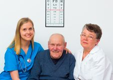 Happy Elderly Person. Happy elderly men at the nursing home with his caregivers stock photos