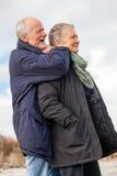 Happy elderly senior couple walking on beach Royalty Free Stock Images