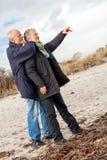 Happy elderly senior couple walking on beach Stock Photography