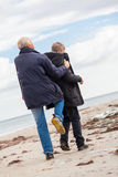 Happy elderly senior couple walking on beach Royalty Free Stock Photos