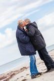 Happy elderly senior couple walking on beach Stock Images