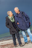 Happy elderly senior couple walking on beach Royalty Free Stock Photos