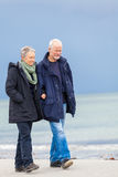 Happy elderly senior couple walking on beach Stock Photo