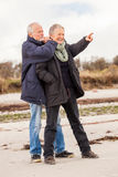 Happy elderly senior couple walking on beach Royalty Free Stock Photo