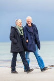 Happy elderly senior couple walking on beach Royalty Free Stock Images