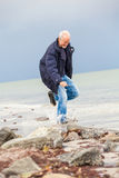 Happy elderly senior couple walking on beach Stock Photos