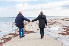 Happy elderly senior couple walking on beach Stock Image