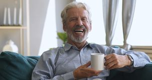 Happy senior man drinking tea on sofa looking at camera