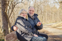 Happy Elderly Senior Romantic Couple Relaxing. In the nature. Old people sitting on the bench portrait outdoor winter autumn season stock photography
