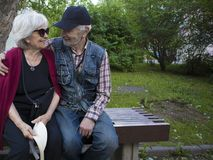 Happy elderly smiling couple sitting on the bench in the park royalty free stock image