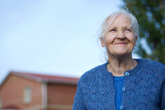 Happy elderly woman. Building on the background Royalty Free Stock Photography