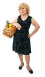 Happy elderly woman with basket of fruits Stock Images