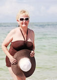 Happy elderly woman on beach. A smiling senior woman by the ocean wearing swim suit holding sun hat royalty free stock photography