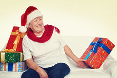 Happy elderly woman with christmas box gift - holiday concept Stock Images