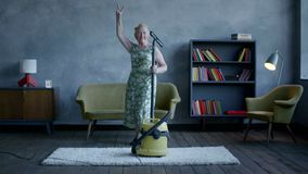 Happy elderly woman dancing with a vacuum cleaner, home fun.  stock footage