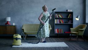 Happy elderly woman dancing with a vacuum cleaner, home fun.  stock video