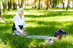 Happy elderly woman doing recreation activities in summer forest Stock Photos