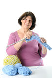 Happy elderly woman is engaged in knitting. Royalty Free Stock Photos