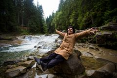 Happy elderly woman enjoying the nature near a mountain stream. In autumn Royalty Free Stock Photography