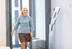 Happy elderly woman enters office door Stock Photos